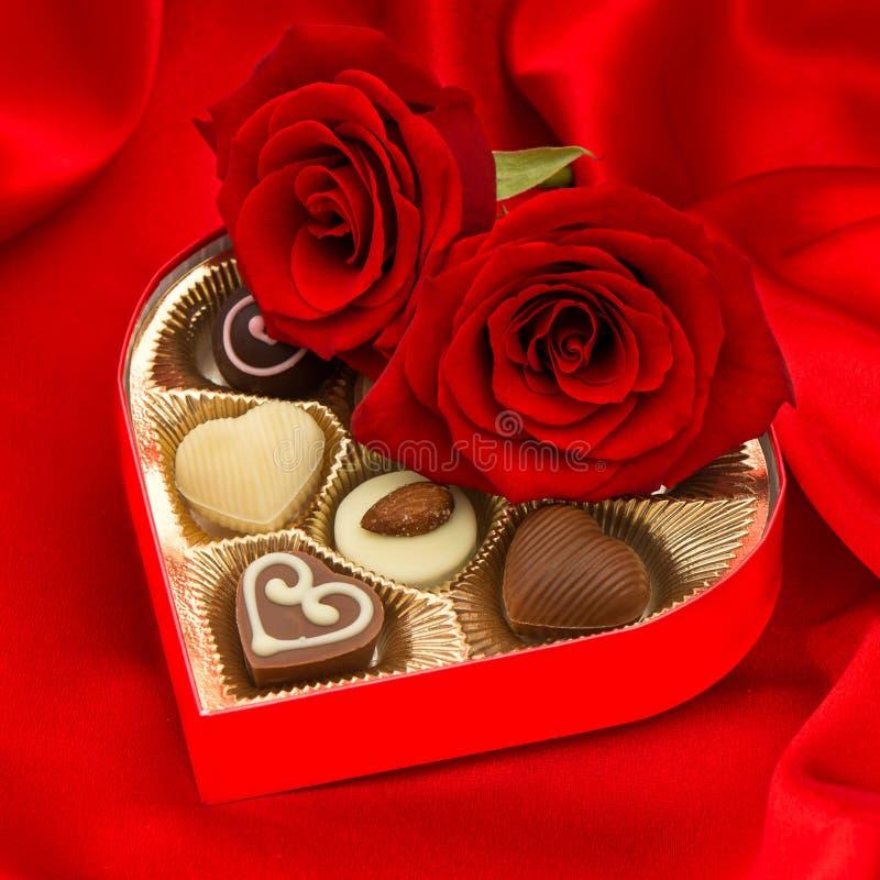 Rote Rosen und köstliche Schokoladenpralinen stockfoto