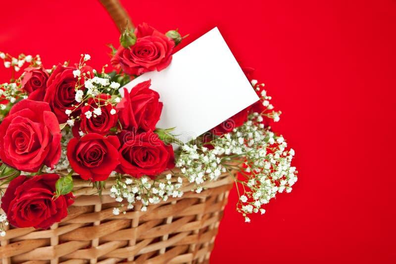 Rote Rosen und Karte im Korb stockfotos