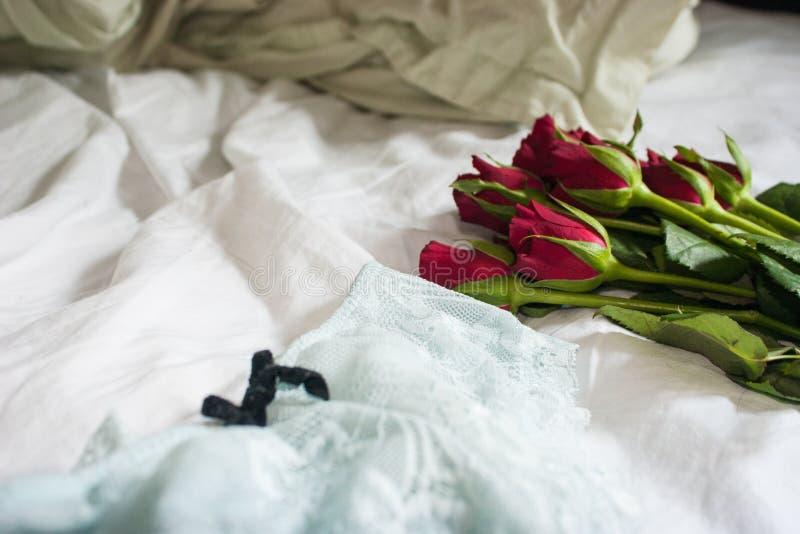 Rote Rosen und Lacy Lingerie auf geknitterten Blättern lizenzfreie stockfotografie