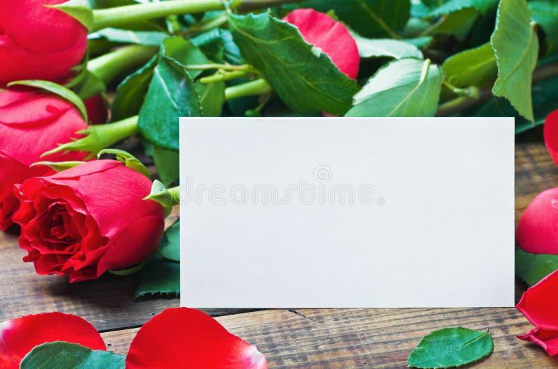 Rote Rosen und weiße Karte mit einem Platz für einen Glückwunschtext stockbilder