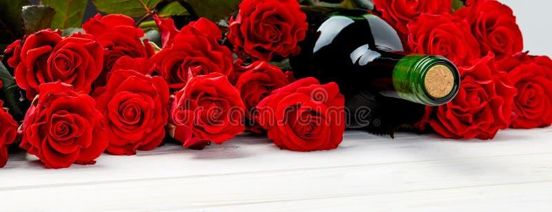Rote Rosen und Wein auf weißem Hintergrund stockbilder