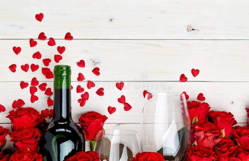 Rote Rosen und Wein auf weißem Hintergrund stockfoto