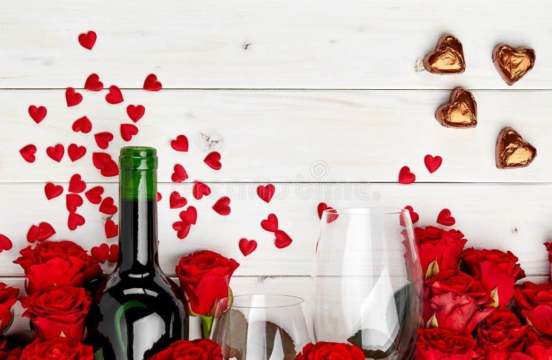 Rote Rosen und Wein auf weißem Hintergrund stockbild