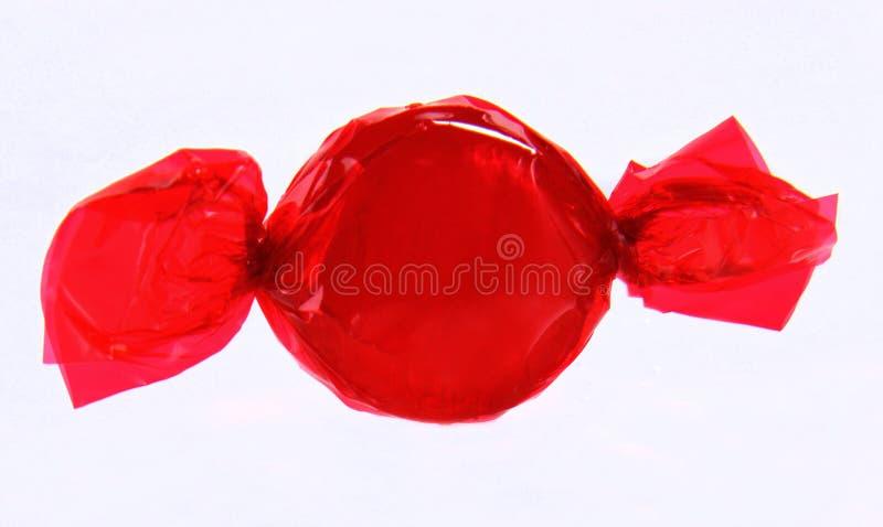 Rote Süßigkeit in der Verpackung auf weißem Hintergrund stockbild