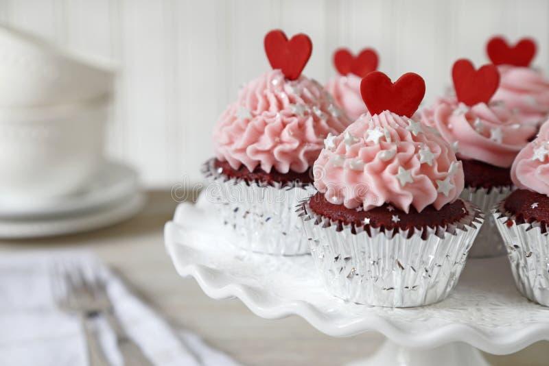 Rote Samtkleine kuchen mit roten Herzen lizenzfreie stockbilder