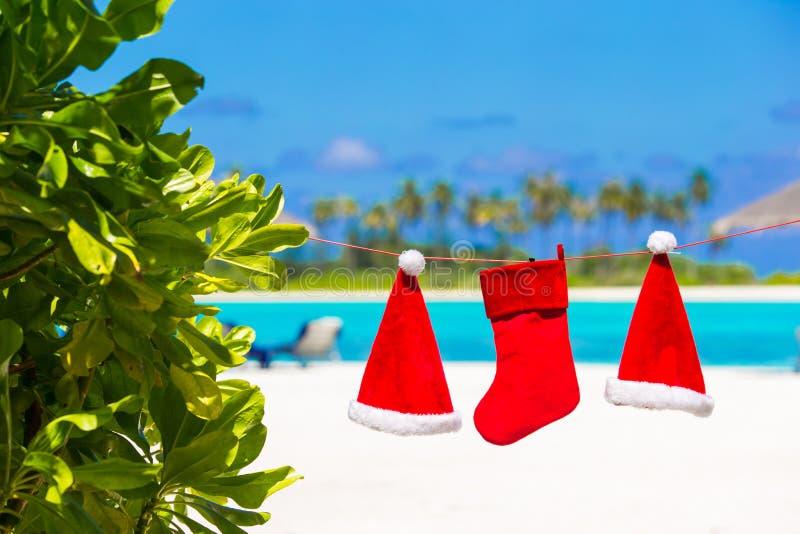 Rote Sankt-Hüte und Weihnachtsstrumpf, der an hängt lizenzfreie stockfotos