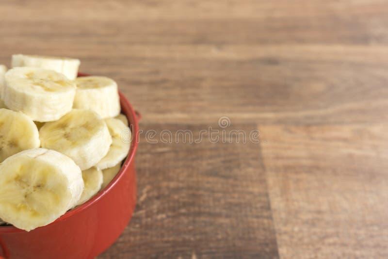 Rote Schüssel mit Bananenscheiben auf hölzernem Hintergrund lizenzfreies stockbild