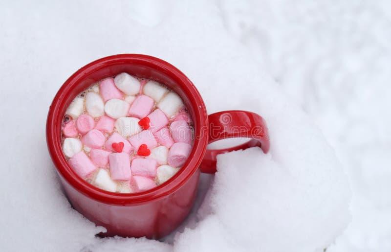 Rote Schale heiße Schokolade mit Eibischsüßigkeiten im Schnee Warmes Kakaogetränk Hallo Februar- oder Valentinsgruß-Tageskonzept stockfoto