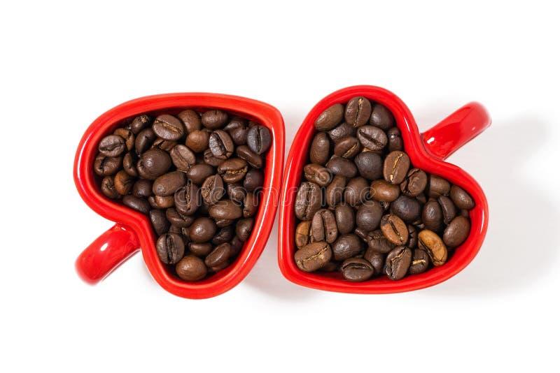 Rote Schalen in Form von Herzen mit Kaffeebohnen auf Weiß lizenzfreie stockfotos
