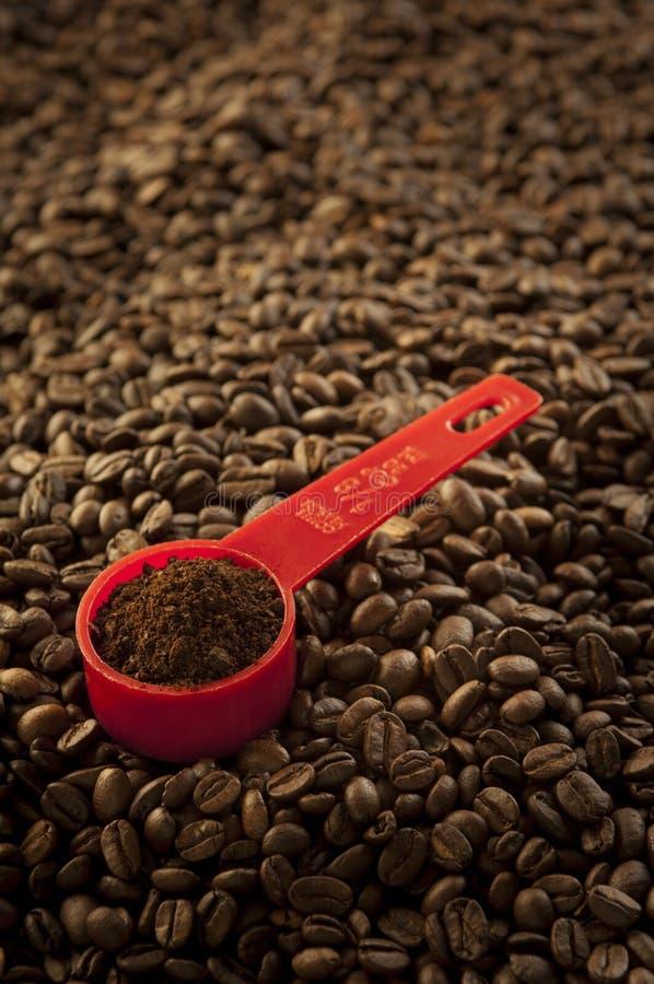 Rote Schaufel und Kaffeebohnen lizenzfreie stockbilder