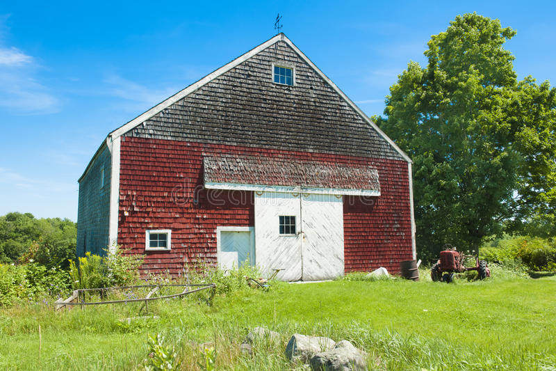 Rote Scheune und alter Traktor in Maine lizenzfreie stockfotos