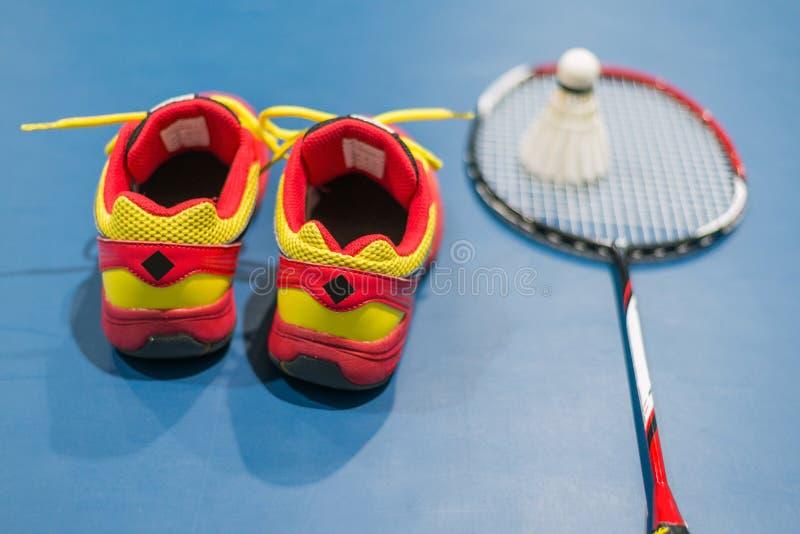 Rote Schuhe des Badminton mit unscharfem Federball und Schläger auf Gericht lizenzfreies stockbild