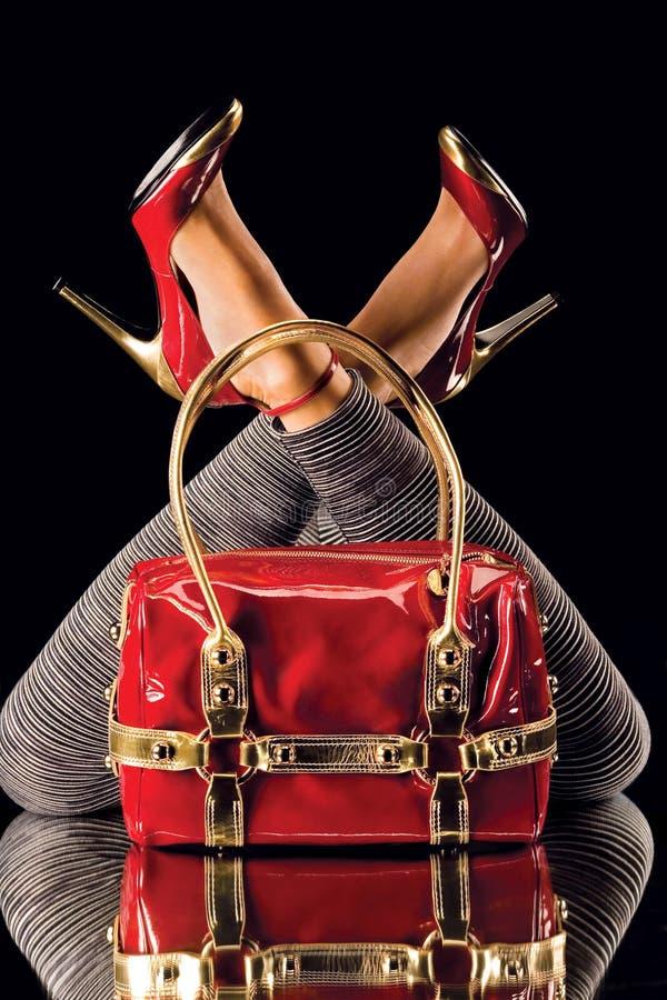 Rote Schuhe und Beutel auf Spiegel lizenzfreie stockfotografie