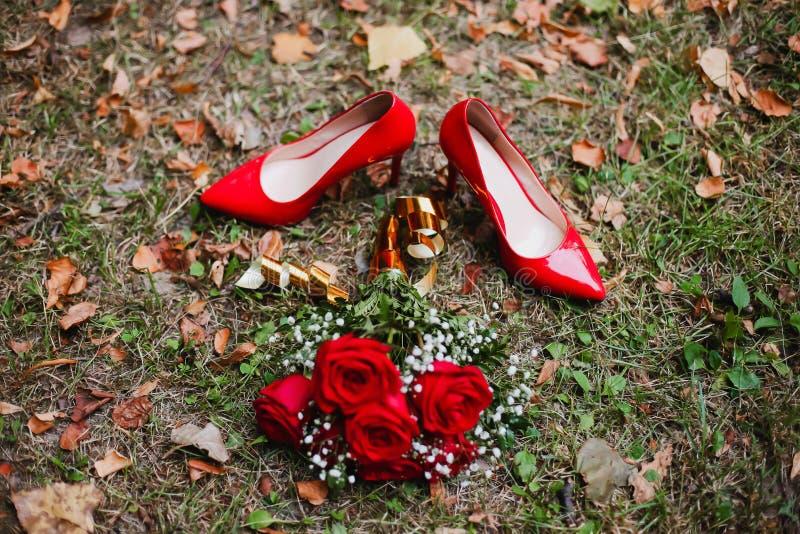 Rote Schuhe und Heiratsblumenstrauß von roten Rosen auf dem Gras Brautdetails stockbilder