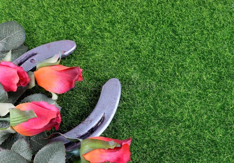 Rote Seidenrosen, ein Hufeisen- und künstliches grünes Gras für die Ausführung das vollblütige Rennen nannten das Kentucky Derby stockfoto