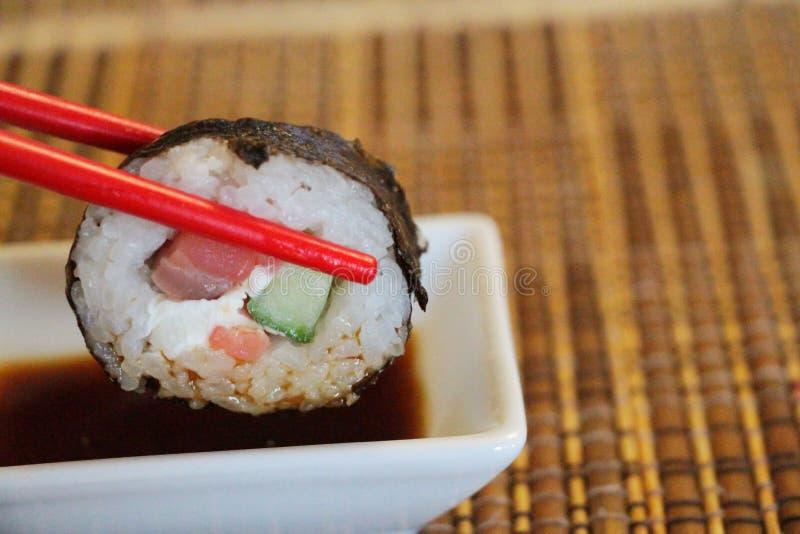 Rote shopsticks hält maki Sushi in einer Luft stockfotos