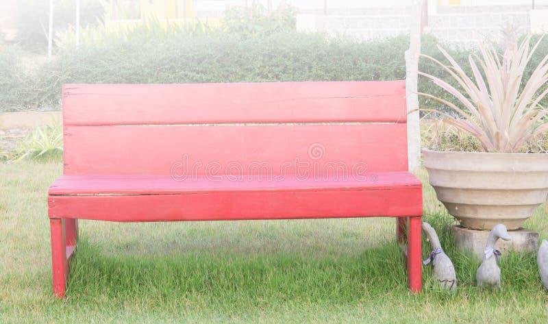 Rote Sitze im Garten lizenzfreie stockfotos