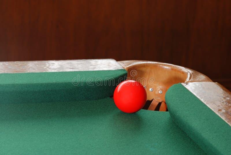 Rote Snooker-Kugel durch Corner Pocket lizenzfreie stockfotos