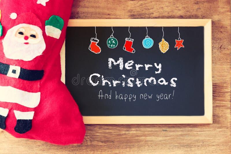 Rote Socke und Tafel mit den fröhlichen grüßenden christams und den bunten Ikonen Feiertagshintergrund mit Tannenbaum und Gruß si lizenzfreie stockfotos