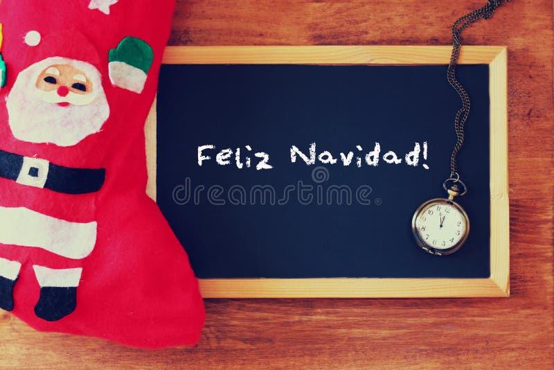 Rote Socke und Tafel mit feliz navidad Gruß Feiertagshintergrund mit Tannenbaum und Gruß simsen stockbild