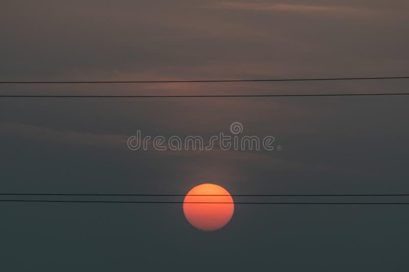 Rote Sonne, die hinter HochspannungsstromStromleitungen an der Dämmerung steigt lizenzfreies stockbild