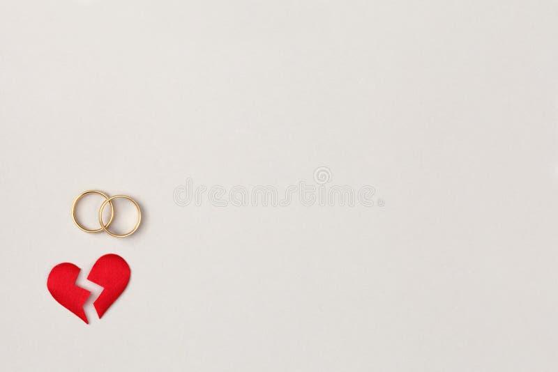 Rote Spalte des defekten Herzens in zwei Stücken mit Paaren von goldenen Eheringen, von Draufsicht, von flachem Lage-, Scheidungs stockfoto
