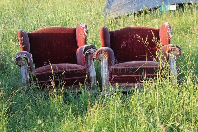 Rote Stühle im Gras stockfotografie