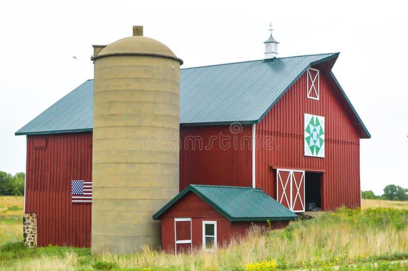 Rote Steppdecken-Scheune mit einer amerikanischen Flagge auf der Seite stockbild