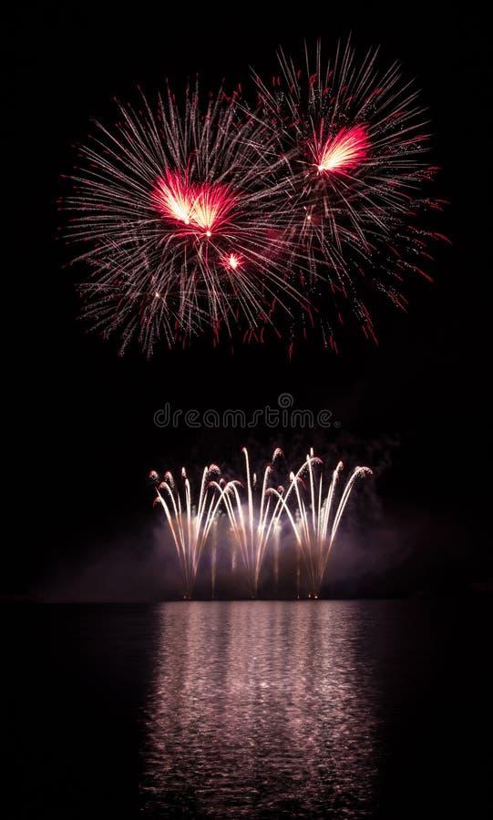 Rote Sterne und Goldbrunnen von den reichen Feuerwerken über Brnos Verdammung mit Seereflexion stockfoto