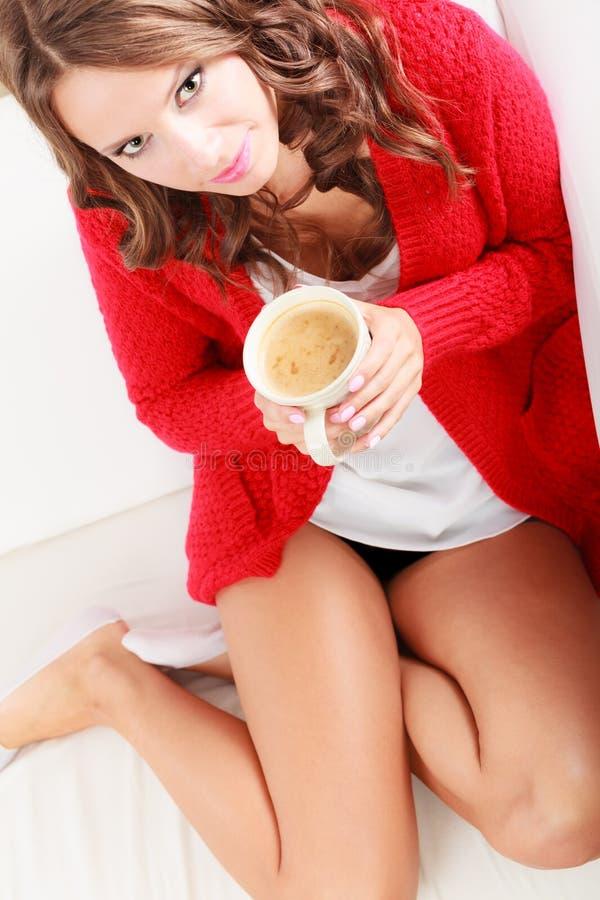 Rote Strickjacke des Mädchens hält Becher mit Kaffee stockbilder