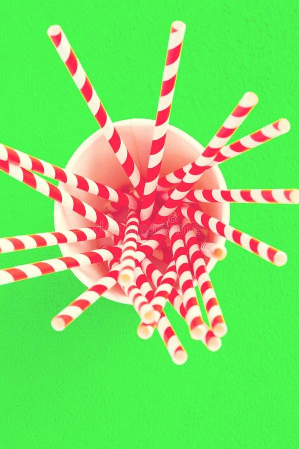 Rote Strohe für Saft in einer Papierschale auf einem grünen Hintergrund tonen lizenzfreies stockbild