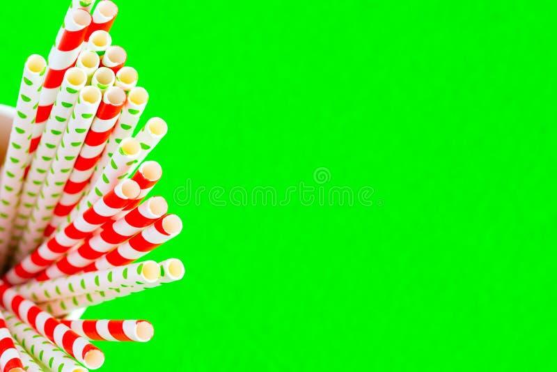 Rote Strohe für Saft in einer Papierschale auf einem grünen Hintergrund vom links lizenzfreies stockbild