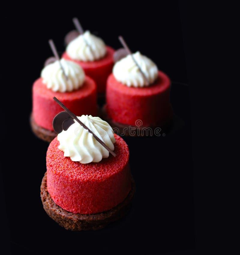 Rote strukturierte Nachtische auf Schokoladenkuchenbasis mit gepeitschtem ganache stockbilder