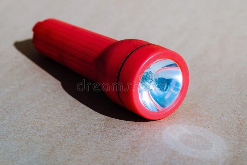 Rote Taschenlampe auf einem Papphintergrund stockbild