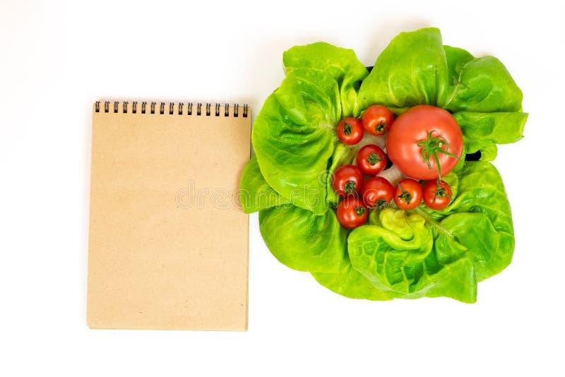 Rote Tomaten im Kopfsalat lokalisiert auf weißem Hintergrund nahe bei Notizblock Zusammensetzung von roten Tomaten in den Kopfsal stockfotografie