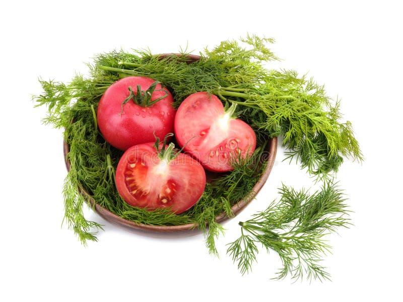 Rote Tomaten mit frischem Dill in einem hölzernen Korb, lokalisiert auf einem weißen Hintergrund Vegetarisches Nahrungsmittelkonz stockfoto