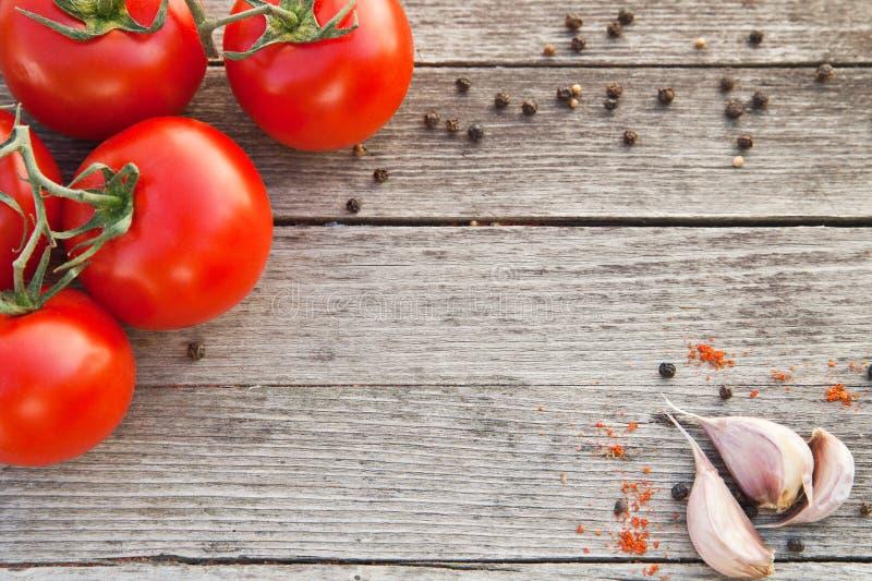 Rote Tomaten mit Pfeffer und Knoblauch auf altem Holz lizenzfreies stockbild