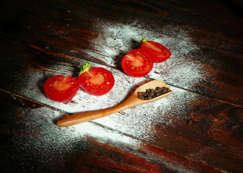 Rote Tomaten neben Pfeffern auf hölzernem Brett lizenzfreie stockfotos