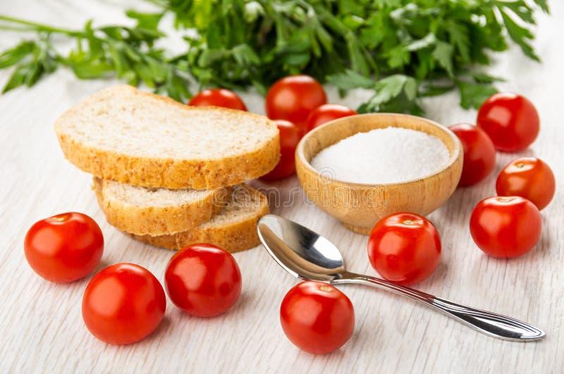 Rote Tomatenkirsche, Schüssel mit Salz, Stücke Brot, Löffel, Petersilie auf Tabelle stockfotografie