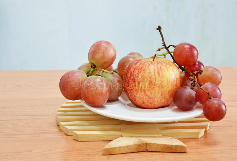 Rote Traube und Apfel auf Teller lizenzfreie stockbilder