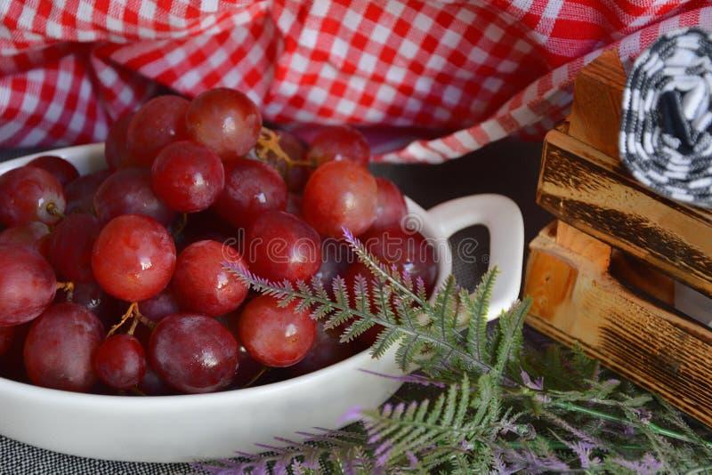 Rote Trauben mit Wassertropfen in weißer Platte lizenzfreies stockfoto