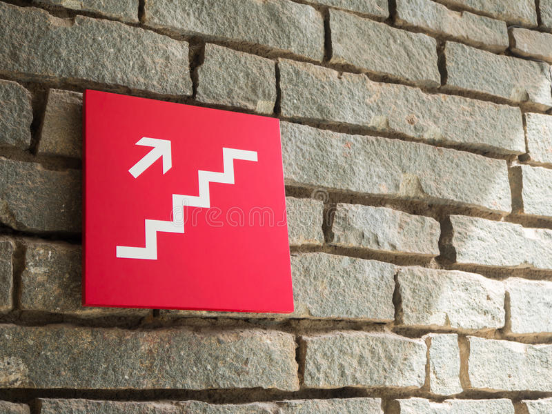 Rote Treppe, die oben Zeichen auf Wandziegelstein geht stockfotos