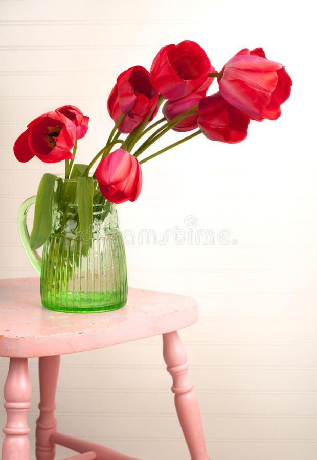 Rote Tulpen auf rosafarbenem Schemel mit Vignetted Korn-Vorstand lizenzfreie stockfotografie