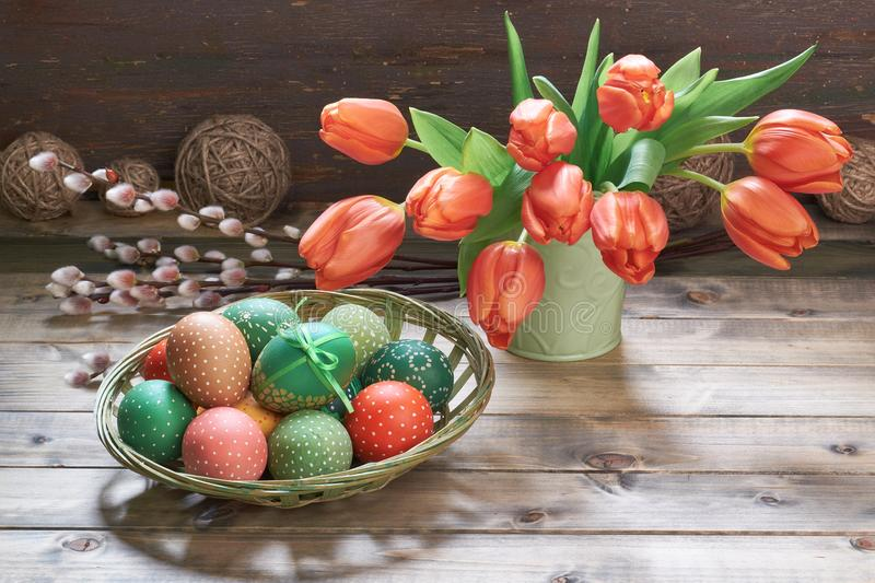 Rote Tulpen, Ostereier und Frühjahrdekorationen auf rustikalem wo stockbild