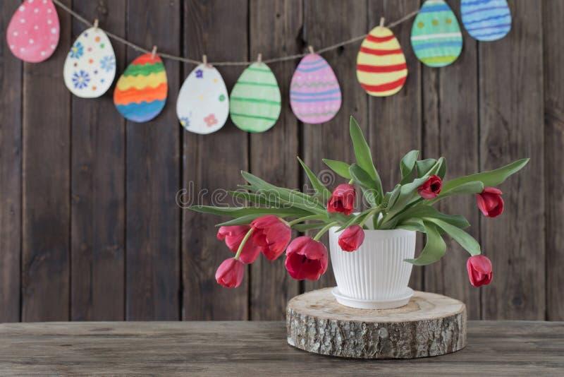 Rote Tulpen und gemalte Papiereier auf hölzernem Hintergrund stockfotos