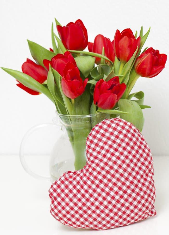 Rote Tulpen und heart-shaped Kissen lizenzfreie stockfotos