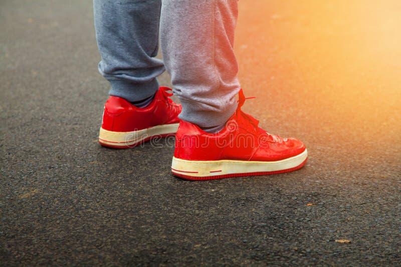 Rote Turnschuhe sind Asphalt mit Sonnenlicht im Rahmen lizenzfreies stockfoto