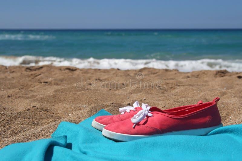 Rote Turnschuhe und blaue Decke auf schönem Strand stockbilder