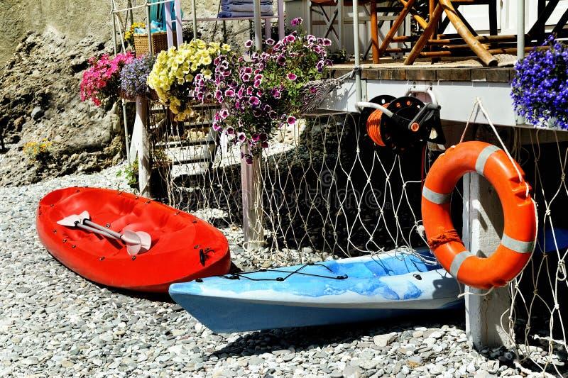 Rote und blaue Kajaks mit Rettungsleine auf Meer setzen auf den Strand lizenzfreie stockfotos