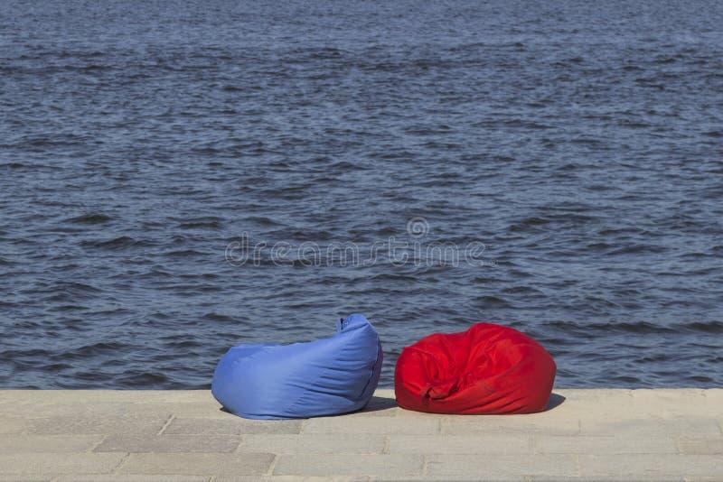 Rote und blaue Strandbohnentaschen auf der Flussbank Restzone lizenzfreie stockbilder